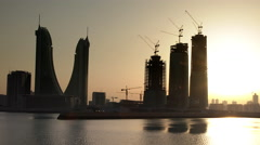 Sunset in the city with new construction skyline - Bahrain - Zoom Out Stock Footage