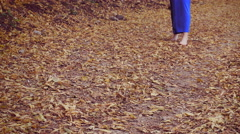 Detail of a barefooted woman, long dress, foliage Stock Footage