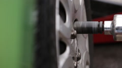 Mechanic twists the hubcaps on the wheels Stock Footage
