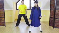 Teacher of martial arts showing form to learner behind 4K Stock Footage