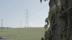 A shot of large electricity pylons in the British countryside on a summers day Stock Footage