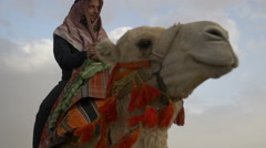Arab male traditional headdress robe riding his camel over desert - stock footage