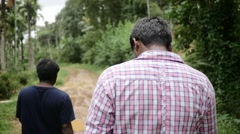 Indian man walking through muddy road Stock Footage