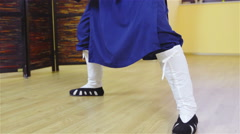 Person legs with traditional shoes in blue uniform make a squat form 4K Stock Footage