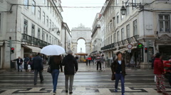 Stock Video Footage of Rua Augusta Arch street, people walk with umbrellas, Lisbon, Portugal