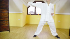 Man in white uniform training martial arts forms alone 4K Stock Footage