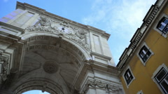 View under Rua Augusta Arch clock, bright blue sky, pan left, Lisbon, Portugal - stock footage