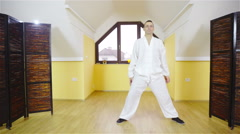 Person in white uniform practicing meditation martial arts form indoors 4K Stock Footage