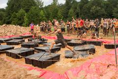 Competitors Run Across Floating Platforms At Extreme Obstacle Course Race - stock photo