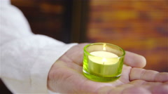 Burning candle in person hand holding still close up 4K Stock Footage