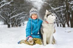 happy boy hugging dog or husky outdoors in winter day - stock photo