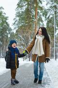 Happy family in winter clothing. Smiling mother and son walk at the park Stock Photos