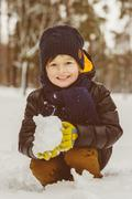 The concept of winter activities . Happy cheerful boy playing snow outdoor - stock photo