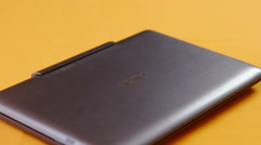 Compact silver laptop on orange surface Stock Footage