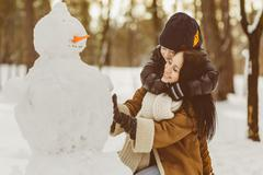 Happy family in warm clothing. Smiling mother and son making a snowman outdoor - stock photo