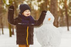The concept of winter activities . Happy boy making snowman outdoor - stock photo