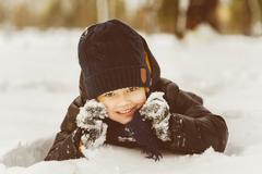 Little boy having fun in the snow Stock Photos