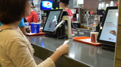 Woman paying for the order in KFC - stock footage
