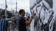 People watching at working graffiti artists - stock footage