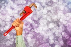 Hand of plumber with a wrench. Stock Photos