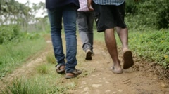 Indian friends walking through muddy road Stock Footage
