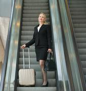 Business woman standing on escalator with travel bags - stock photo