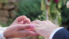 Groom puts on the ring on the finger of the bride Stock Footage