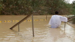 A woman is entering the baptismal site Yardenit on the Jordan river Stock Footage