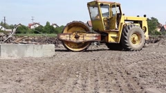 Huge road roller with spikes is compacting soil at construction site. Stock Footage