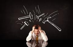 Depressed businessman sitting under hammer marks - stock photo