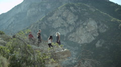 Four people on a mountain rock outcropping. - stock footage