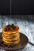 Stack of homemade pancakes with black currant and honey on brown plate Stock Photos