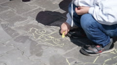 Little boy drawing with chalk on asphalt - stock footage