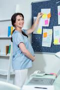 Pregnant woman sticking note on board Stock Photos