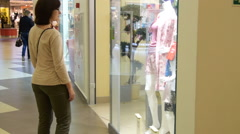 Young woman looking at shop-window in trade center Stock Footage
