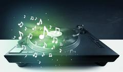 Turntable playing music with audio notes glowing - stock photo