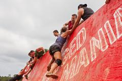 Stock Photo of Competitors Struggle To Climb Wall In Extreme Obstacle Course Race