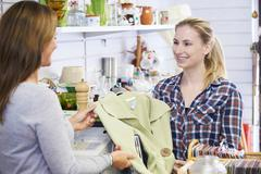 Customer Buying Clothing In Charity Shop - stock photo