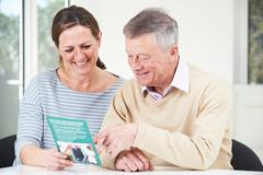 Senior Man With Adult Daughter Looking At Brochure For Retirement Home Stock Photos