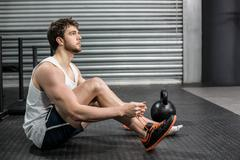Fit man tying up her shoe laces - stock photo