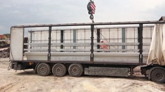 Mobile crane is unloading pillars. - stock footage