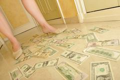 Woman's legs walking on US Currency dollar banknotes on a floor - personal we Stock Photos