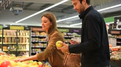 Couple at the grocery store buying fruits and vegetables - stock footage
