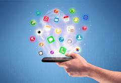 Hand holding tablet phone with app icons - stock photo