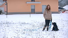 Woman and dog posing on lawn covered with snow Stock Footage