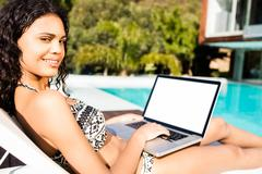 Fit brunette lying on deck chair and using laptop Stock Photos