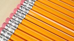 Row of identical sharpened pencils with orange coating. Equality concept, dolly Stock Footage