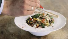 Food style specialist working on the asian pasta in a deep porcelain plate. Stock Footage