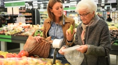 Elderly woman with young woman at the grocery store Stock Footage