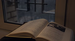 Open book in front of the window. Winter, snow shower. Stock Footage